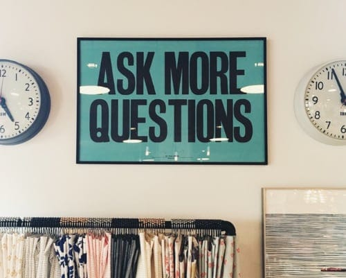 """sign which reads, """"Ask More Questions"""""""
